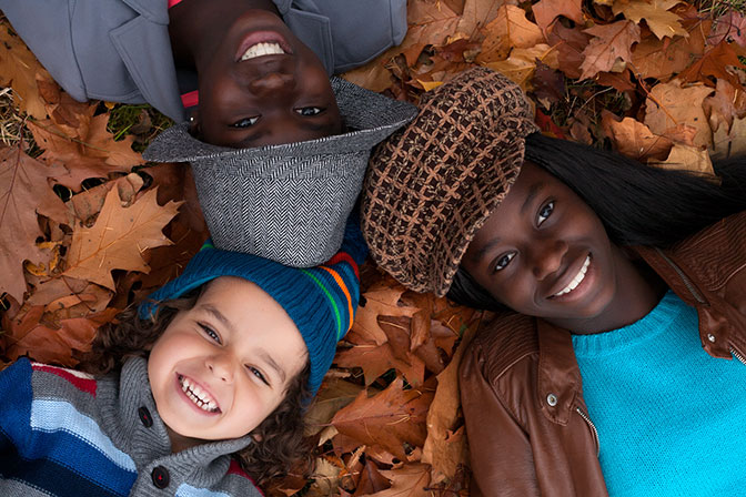 Kids Lying in Autumn Leaves